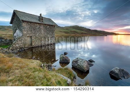 An old stone boat house on the shores of Devoke Water at the foot of Birker Fell in the Lake District in Cumbria