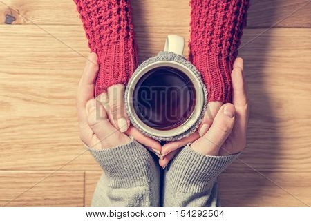 A couple in love warming hands with a hot mug of tea. Wearing cosy woollen jumpers.