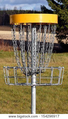 Closeup of disc golf target on disc golf course.