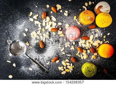 Selection of colorful cakes macarons on a black background, sprinkled with powdered sugar, with whole almonds and almond petals. Copy space, top view