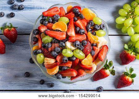 Tasty spring fruit salad on old wooden table