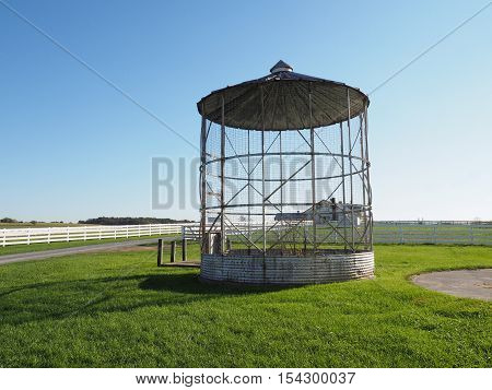 an old grain silo sits unused by a field