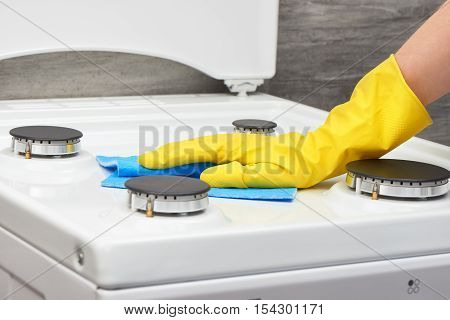 Hand In Yellow Glove Cleaning White Stove With Blue Rag
