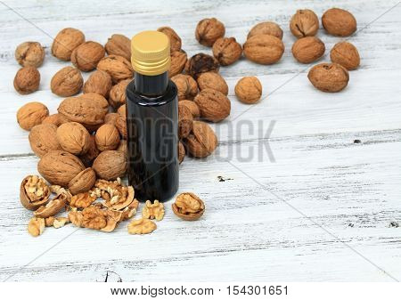 Walnut oil from walnut kernels in a brown bottle walnut shells around it and whole walnuts on the wooden table