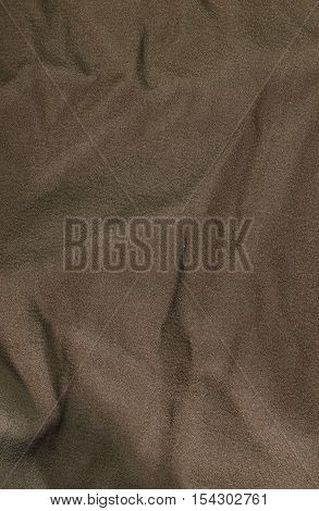 Brown wrinkled fabric texture background. Close up