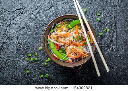 Vegetables with noodles and shrimp on black rock