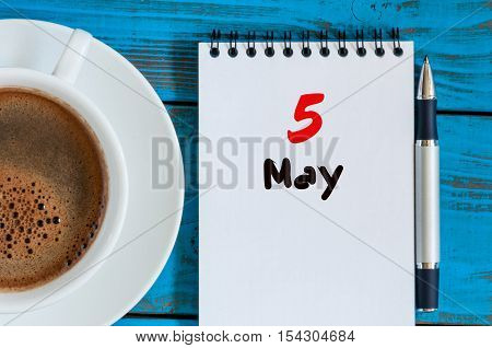 May 5th. Day 5 of month, calendar on white notepad with morning coffee cup at work place background. Spring time, Top view.