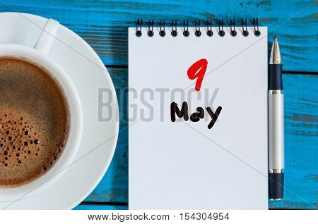 May 9th. Day 9 of month, calendar on white notepad with morning coffee cup at work place background. Spring time, Top view.