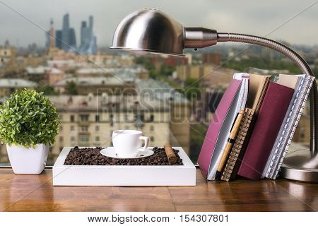 Closeup of wooden windowsill with coffee cup and beans table lamp decorative plant and book with notepads on city background