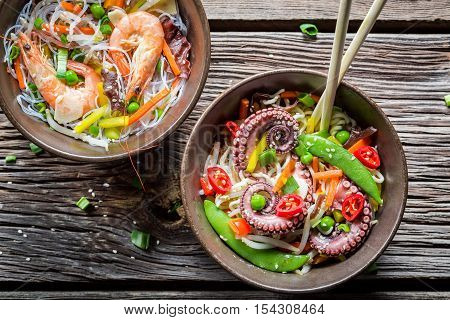Seafood and fresh vegetables with noodles on wooden table