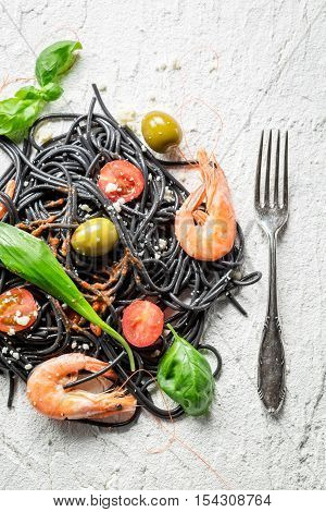 Spaghetti with prawns and black pasta on white rock
