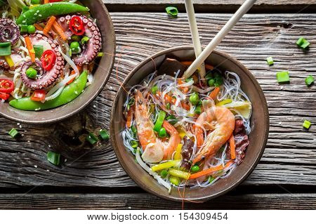 Seafood served with vegetables and noodles on wooden table