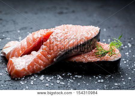 Fresh raw salmon with coarse salt on black rock