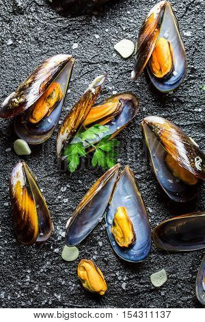 Mussels with garlic and parsley on black rock