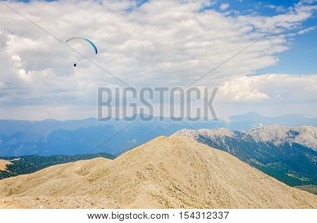 Paraglider flying over mount Tahtali Turkey Kemer. Paragliding in the mountains.