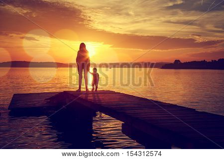 Silhouettes of Young Mother and Her Little Baby Standing on the Pier and Watching Sunset by the Lake. Happy Family Lifestyle. Motherhood and Childhood. Mom and Son. Toned Photo with Bokeh. Copy Space. poster