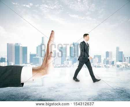 Tiny man walking away from huge human palm on city background