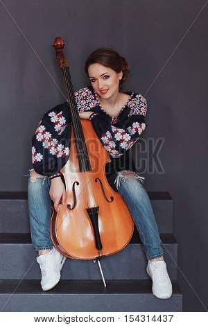 Photo of a beautiful female musician playing a cello. Girl in traditional dress. Woman in vyshyvanka.