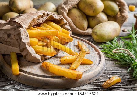 Closeup of homemade fries with salt on wooden table