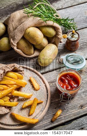 Closeup of fresh homemade French fries on wooden table