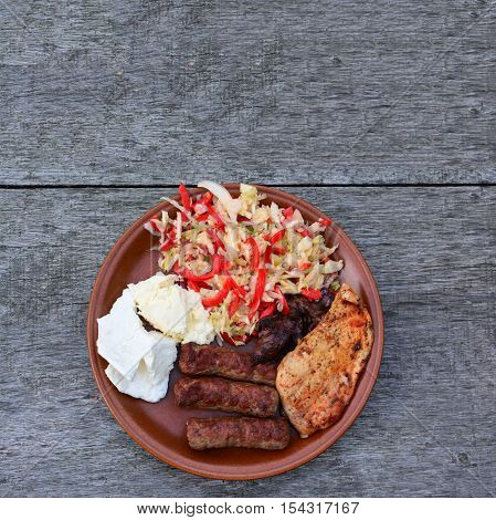 Healthy tasty and strong dish chicken steak and liver cevapcici dairy products and salad in brown ceramic plate on old oak table view from above
