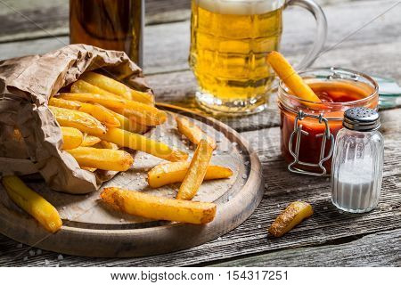 Homemade fresh fries with beer on wooden table