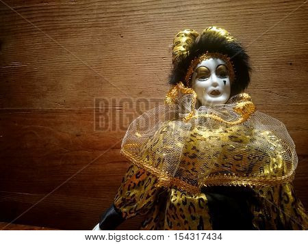 A porcelain harlequin puppet on a wooden background