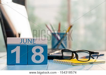June 18th. Day 18 of month, wooden color calendar on account office background. Summer time. Empty space for text.