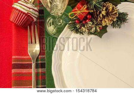 Holiday table setting with Christmas decorations over colorful napkins. Top view. Horizontal.