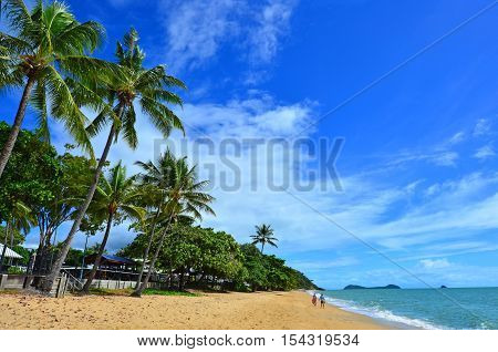 A couple walks on Trinity beach near Cairns in Tropical North Queensland Queensland Australia.