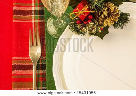Holiday table setting with white plates fork wineglass and Christmas decorations over colorful napkins. Top view. Horizontal.