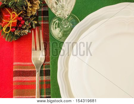 Festive table setting with two white plates fork wineglass and Christmas decorations over colorful napkins. Top view. Horizontal.
