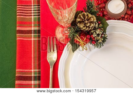 Christmas table setting with porcelain plates fork wineglass and candle. Top view. Horizontal.