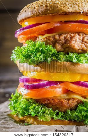 Closeup of tasty homemade big burger on wooden table