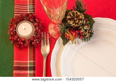 Festive table setting with porcelain plates fork wineglass Christmas decorations and burning candle. Top view. Horizontal.