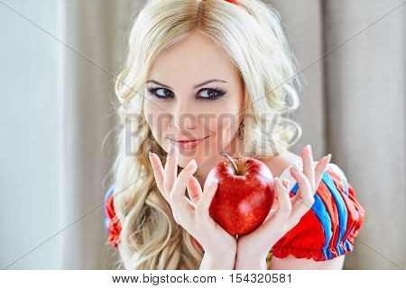 Positive woman holding an apple in her hands