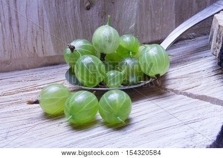 Gooseberries On A Spoon.  In  Wooden  And Background.