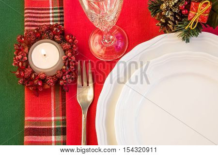 Holiday table setting with porcelain plates fork wineglass Christmas decorations and burning candle. Top view. Horizontal.