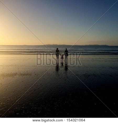 Grandmother Daugther and grandhild walks on the beach during summer holiday on sunset.