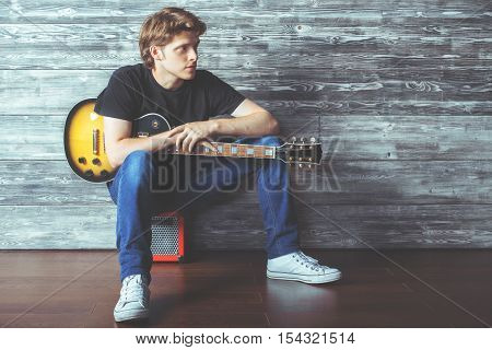 Handsome young guy with electric guitar sitting on amplifier in wooden room. Music concert rehearsal concept
