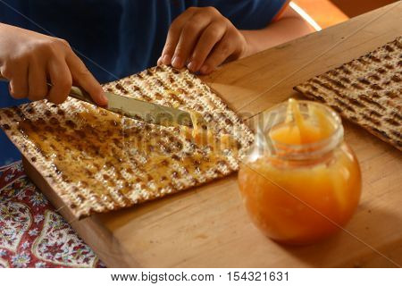 Jewish child hands spread honey on Matzo bread during Passover Jewish holiday.