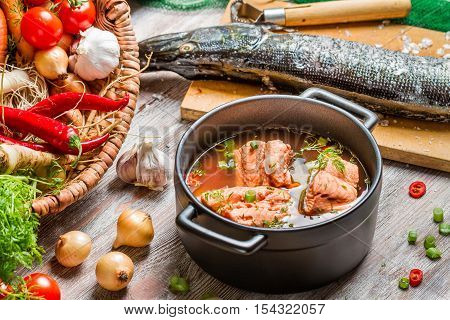 Fresh ingredients for fish soup on wooden table