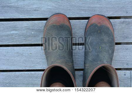 Mans Gardening Gumboots On Wooden Panels