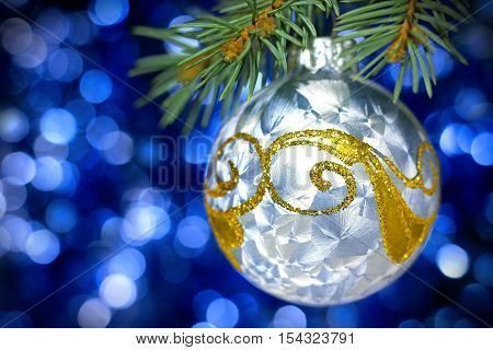 Blue christmas decoration ball with pine blue bokeh background and vignette
