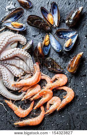 Three kinds of fresh seafood on black rock