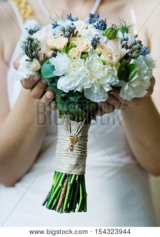 Beautiful wedding bouquet in bride's hand (soft focus)