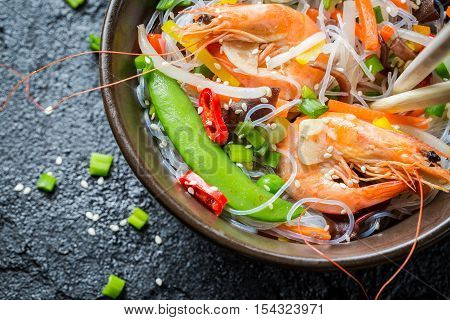 Vegetables served with prawns and noodles on black rock