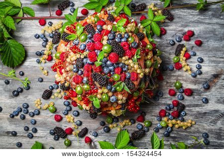 Cake made of fresh wild fruit on wooden table