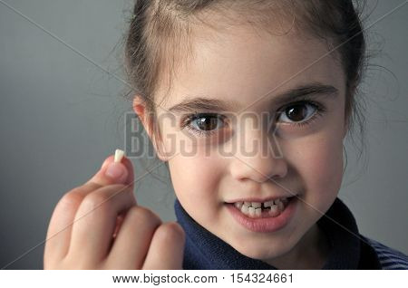Proud Young Girl Holds Her First Falling Milk Teeth
