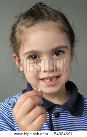 Happy Young Girl Holds Her First Falling Milk Teeth